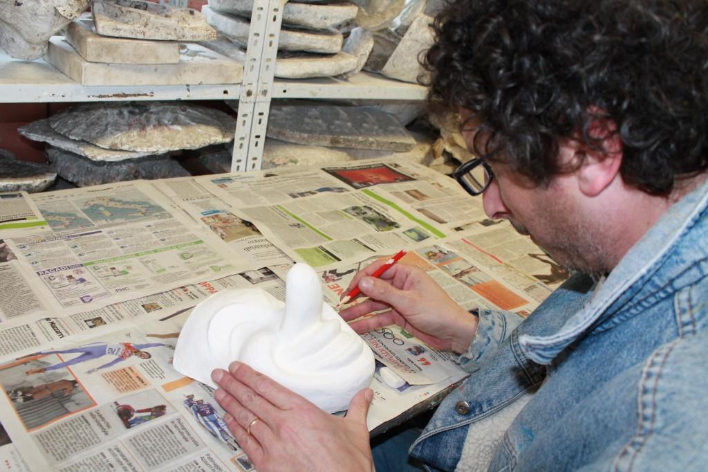 artista al lavoro con la cartapesta