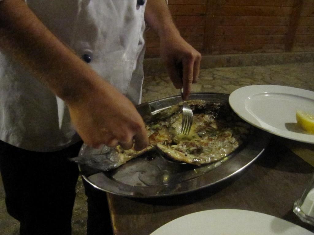 Vincenzo ci pulisce il pesce arrosto.